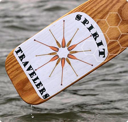 Spirit Travelers logo on a canoe paddle